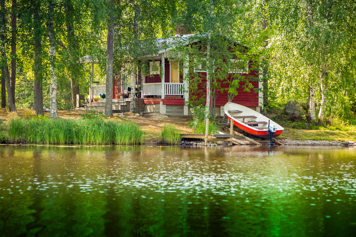 cottage by a lake with a boat